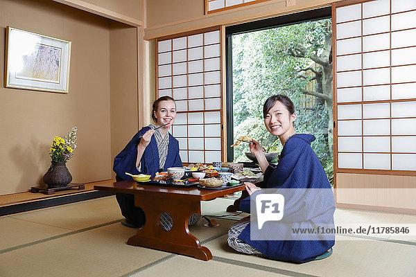 Caucasian woman wearing yukata eating with Japanese friend at traditional ryokan  Tokyo  Japan