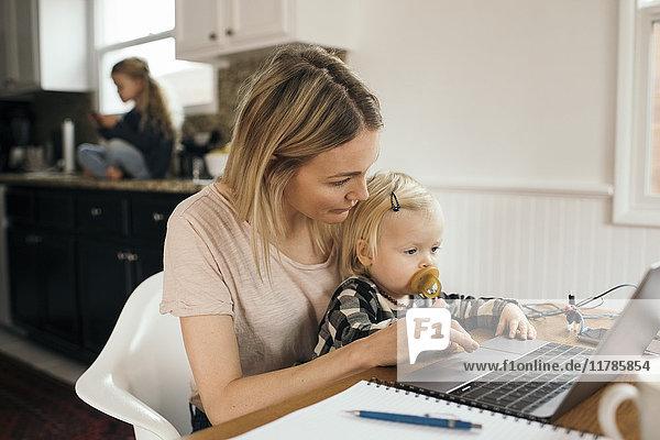 Mittlere erwachsene Frau  die den Laptop benutzt  während ihre Tochter zu Hause auf dem Schoß sitzt.