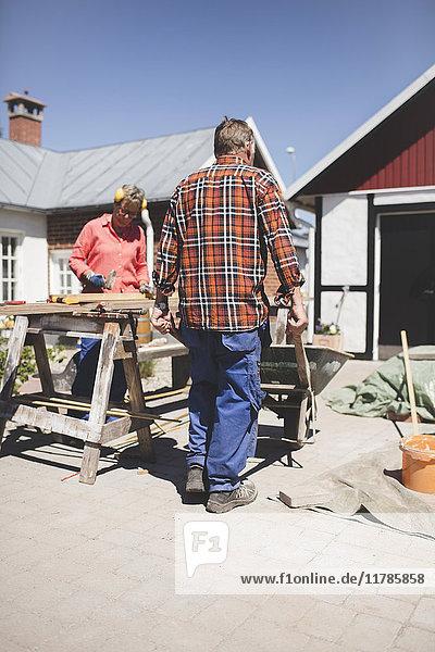 Seniorenpaar bei der Schreinerei auf dem Hof