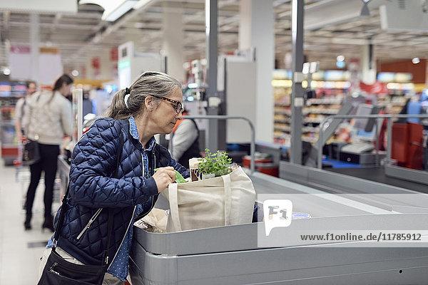 Reife Frau beim Einkaufen an der Kasse im Supermarkt