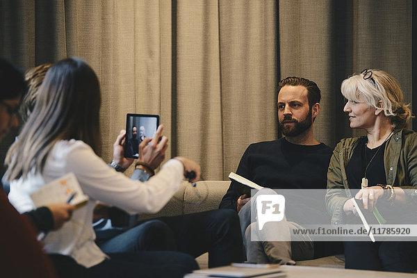 Geschäftsfrau fotografiert Kollegen durch digitales Tablett im Büro