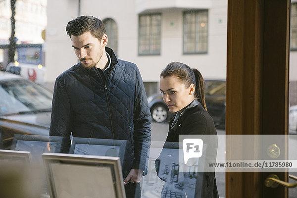 Junges Paar betrachtet Bilderrahmen vom Bürofenster aus gesehen