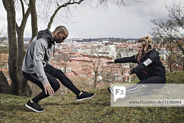 Full length of couple in sportswear exercising on hill
