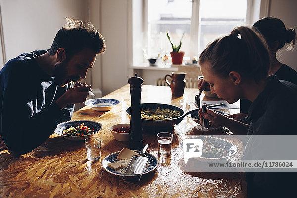 Seitenansicht des Paares beim Nudelessen mit Freundin zu Hause