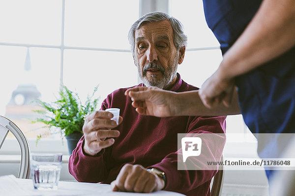 Mittelteil des Hausmeisters  der den älteren Mann zu Hause mit Medikamenten versorgt.