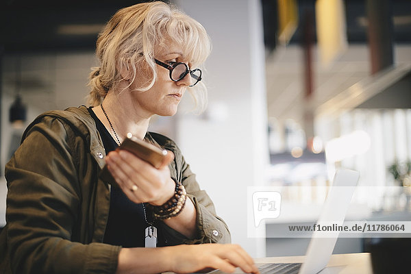 Geschäftsfrau  die ein Smartphone hält  während sie den Laptop am Schreibtisch im Büro benutzt.