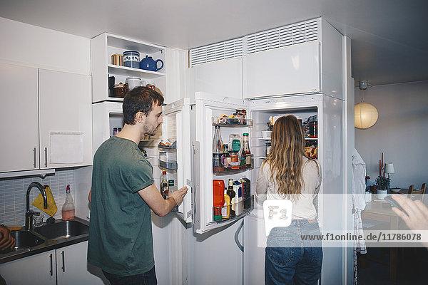 Mann und Frau stehen neben Kühlschränken in der Küche im Studentenwohnheim.