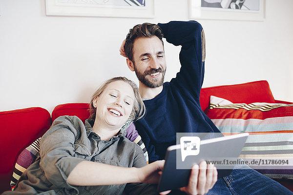 Glücklich  dass ein Paar auf dem Sofa im Wohnzimmer auf ein digitales Tablett schaut.