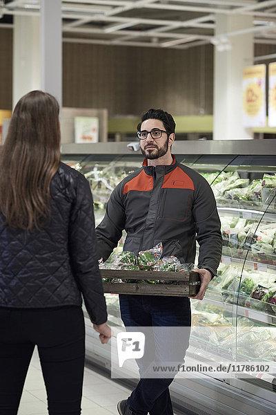 Rückansicht einer Frau im Gespräch mit einem Verkäufer  der Paprika in einer Kiste im Supermarkt hält.