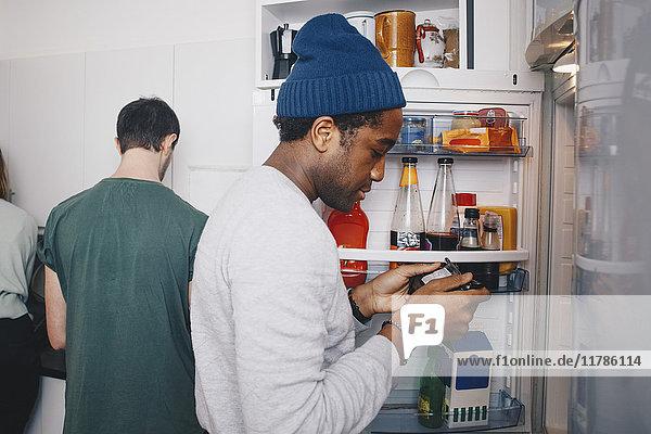 Seitenansicht des Mannes beim Betrachten der Lebensmittelverpackung am Kühlschrank in der Küche