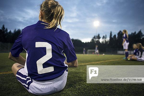 Rückansicht des auf dem Feld sitzenden Mädchens gegen den Himmel