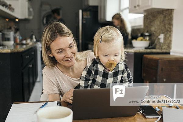 Glückliche Mutter mit Tochter mit Laptop mit Familie im Hintergrund zu Hause