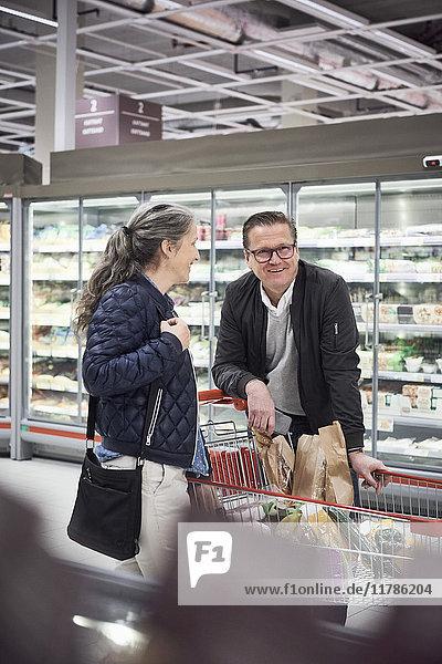 Lächelndes Paar stehend mit Einkaufswagen im Kühlregal im Supermarkt