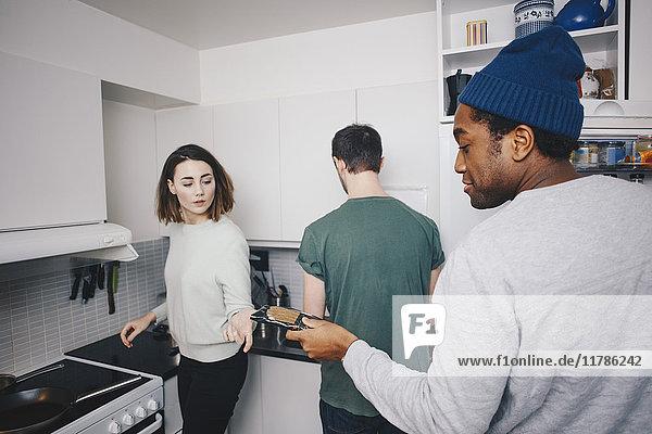 Mann  der dem weiblichen Mitbewohner in der Küche des Studentenwohnheims Essenspakete gibt.