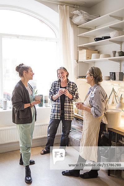 Zufriedene Kolleginnen stehen mit Kaffeebechern im Keramikgeschäft