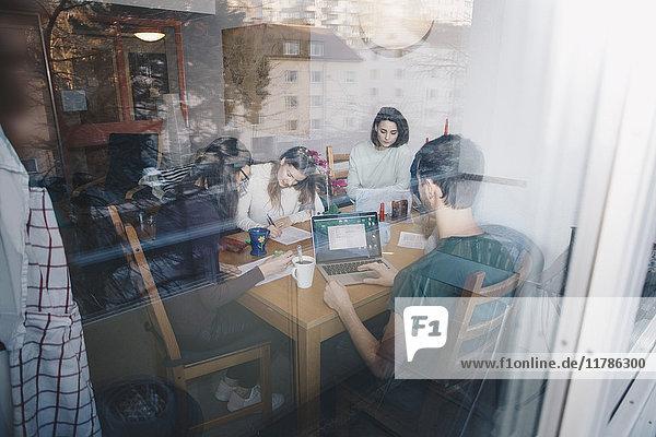 Junge Freunde beim gemeinsamen Lernen im Studentenwohnheim durch ein Glasfenster gesehen
