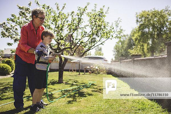Volle Länge der Großmutter  die dem Enkel hilft  Wasser auf die umgebende Wand im Hof zu sprühen.