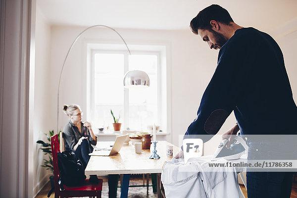Mann bügelt  während Frau auf dem Stuhl sitzt und zu Hause am Esstisch sitzt