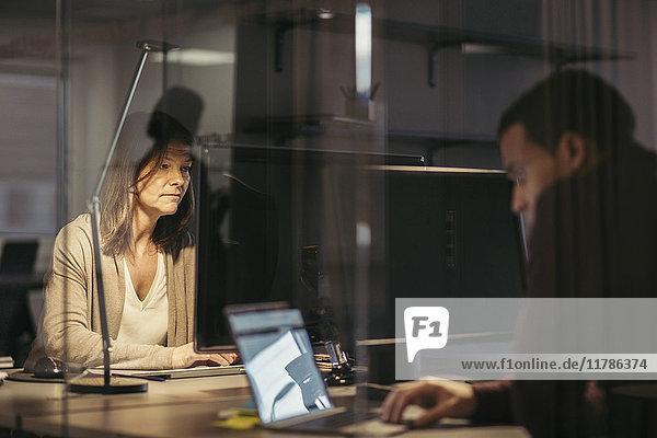 Geschäftskollegen  die Technologie nutzen  während sie spät im Büro arbeiten.