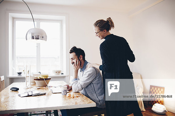 Happy couple looking at laptop on dining table in room