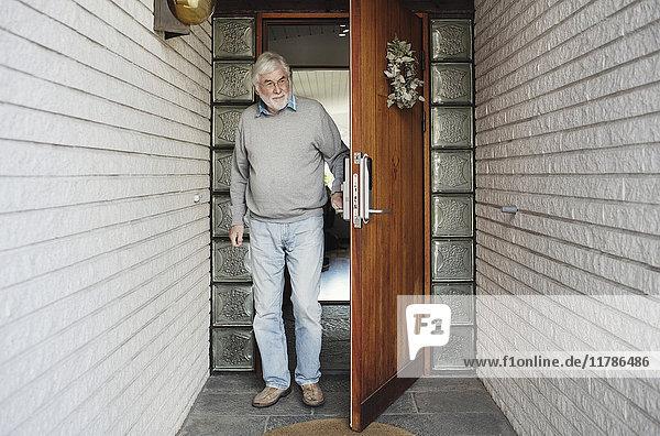Volle Länge des älteren Mannes beim Öffnen der Holztür