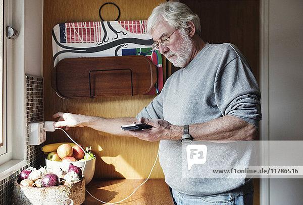 Senior Mann hält Handy  während er das Ladegerät an die Steckdose in der heimischen Küche anschließt.