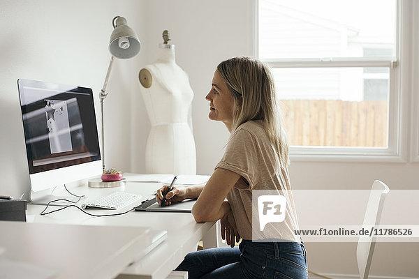 Seitenansicht der kreativen Designerin mit Grafiktablett zu Hause