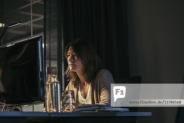 Geschäftsfrau  die den Computer benutzt  während sie im Büro am Schreibtisch sitzt.