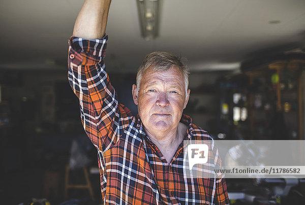 Porträt eines selbstbewussten älteren Mannes in der Werkstatt