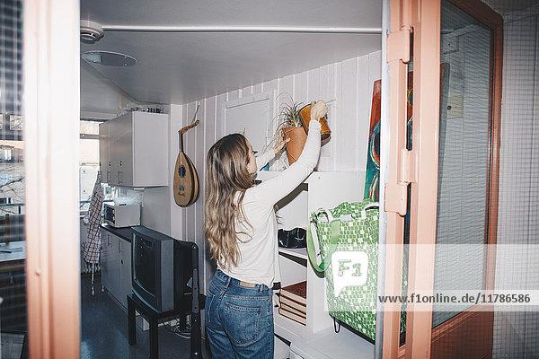 Frau bewässert Topfpflanze im Schlafsaal