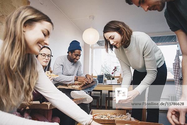 Glückliche junge Freunde essen Pizza im Studentenwohnheim Zimmer