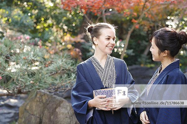 Caucasian woman wearing yukata with Japanese friend at traditional ryokan  Tokyo  Japan