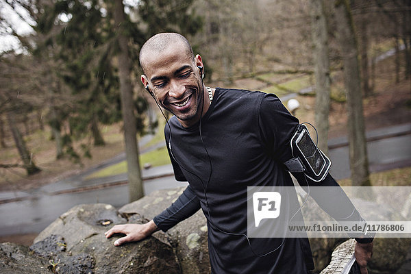 Happy male athlete listening music while exercising by stone wall in forest