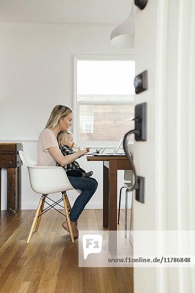 Durchgehende Seitenansicht der Frau mit Tochter bei der Benutzung des Laptops zu Hause