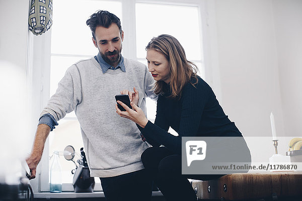 Junge Frau zeigt dem Mann das Handy gegen das Fenster zu Hause
