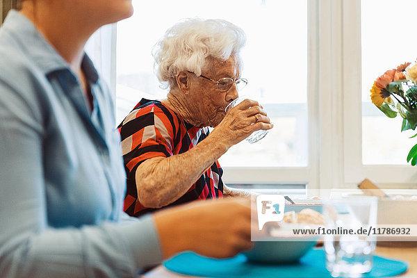 Seniorin trinkt Wasser  während sie mit ihrer Tochter am Esstisch sitzt.
