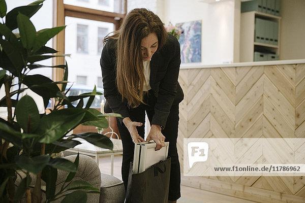 Reife Maklerin  die im Büro das Schild in die Tasche steckt.