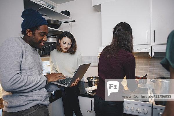 Mann zeigt Laptop einer Freundin in der Küche