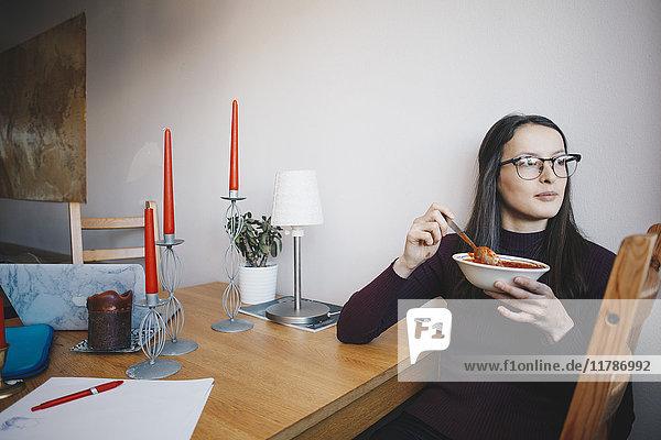 Junge Frau isst Tomatensuppe sitzend auf Stuhl an Tisch gegen Wand im Schlafsaal