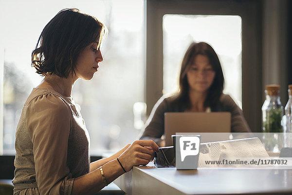 Seitenansicht der Geschäftsfrau beim Lesen des Dokuments am Schreibtisch mit Mitarbeiter im Hintergrund