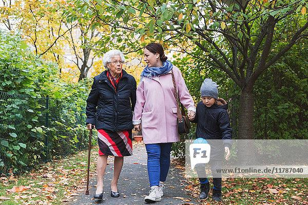 Volle Länge der älteren Frau  die mit Tochter und Urenkel im Park läuft.