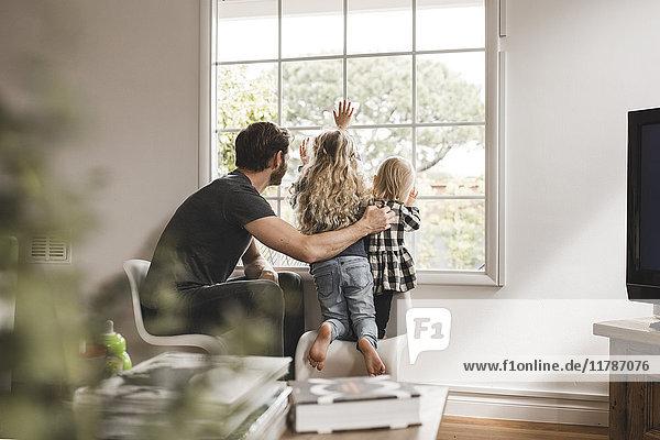 Vater mit Töchtern  die zu Hause durchs Fenster schauen