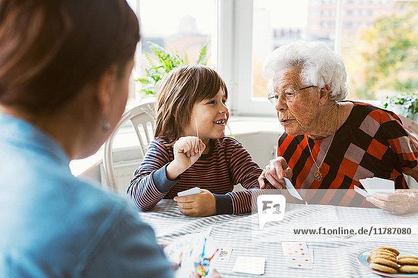 Glücklicher Junge zeigt Spielkarte mit Urgroßmutter zu Hause