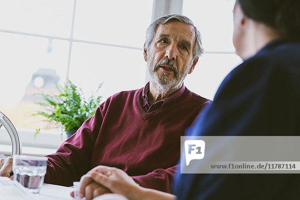 Älterer Mann im Gespräch mit Hauswartin