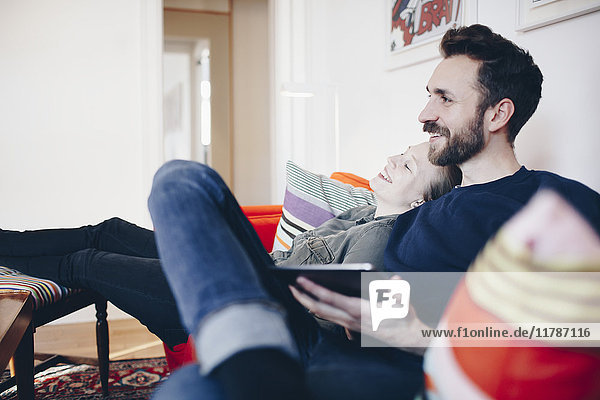 Happy couple sitting on sofa in living room at home