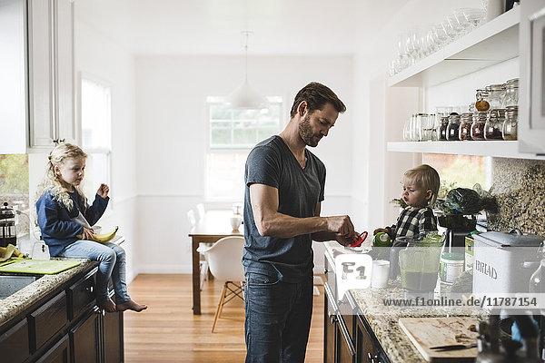 Mittlerer erwachsener Mann mit Töchtern beim Kochen in der Küche zu Hause