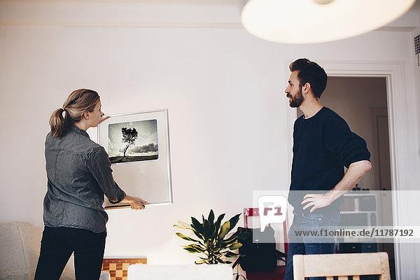Mann und Frau diskutieren zu Hause über Malerei