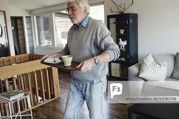 Senior Mann mit Serviertablett beim Spaziergang im Wohnzimmer zu Hause
