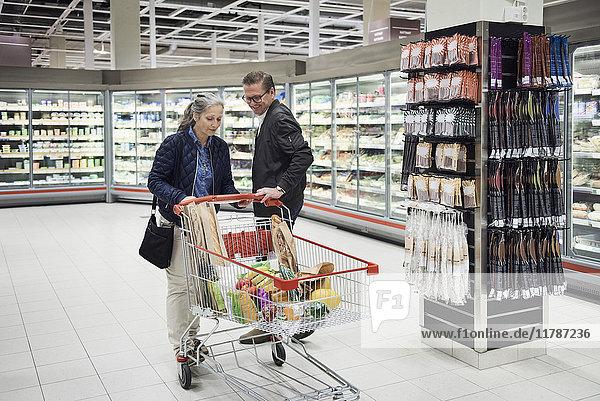 Reife Paare mit Lebensmitteln im Einkaufswagen im Kühlregal des Supermarktes