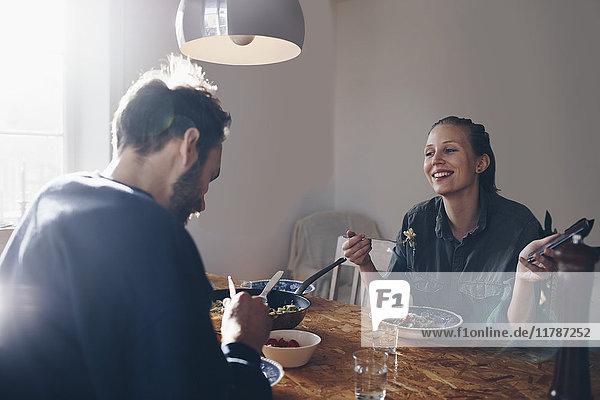 Glückliche Frau mit Handy  die den Mann beim Nudelessen zu Hause ansieht.